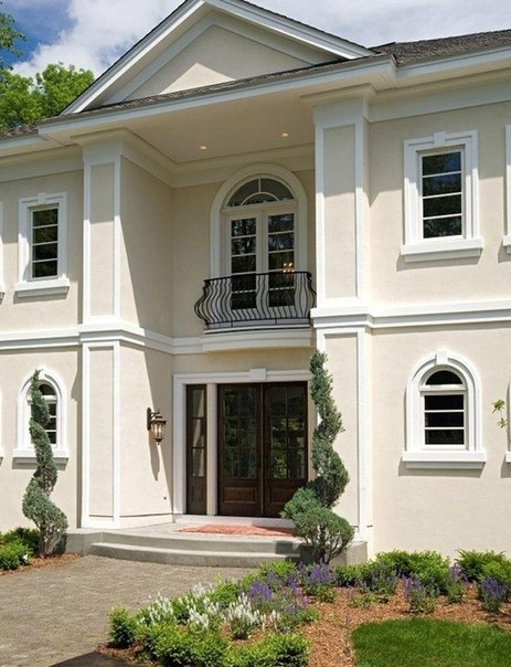 Фасад дома в классическом стиле выглядит торжественно.