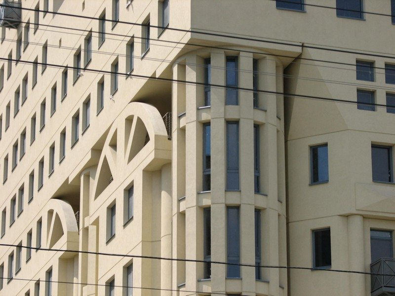 На фото изображен многоэтажный фасад с декоративной штукатуркой