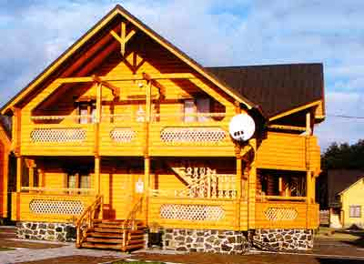 Отделка фасада деревянного дома краской на алкидной основе в сочетании с каменным декором цоколя