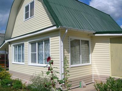 Стены и фронтон деревянного дома отделаны сайдингом