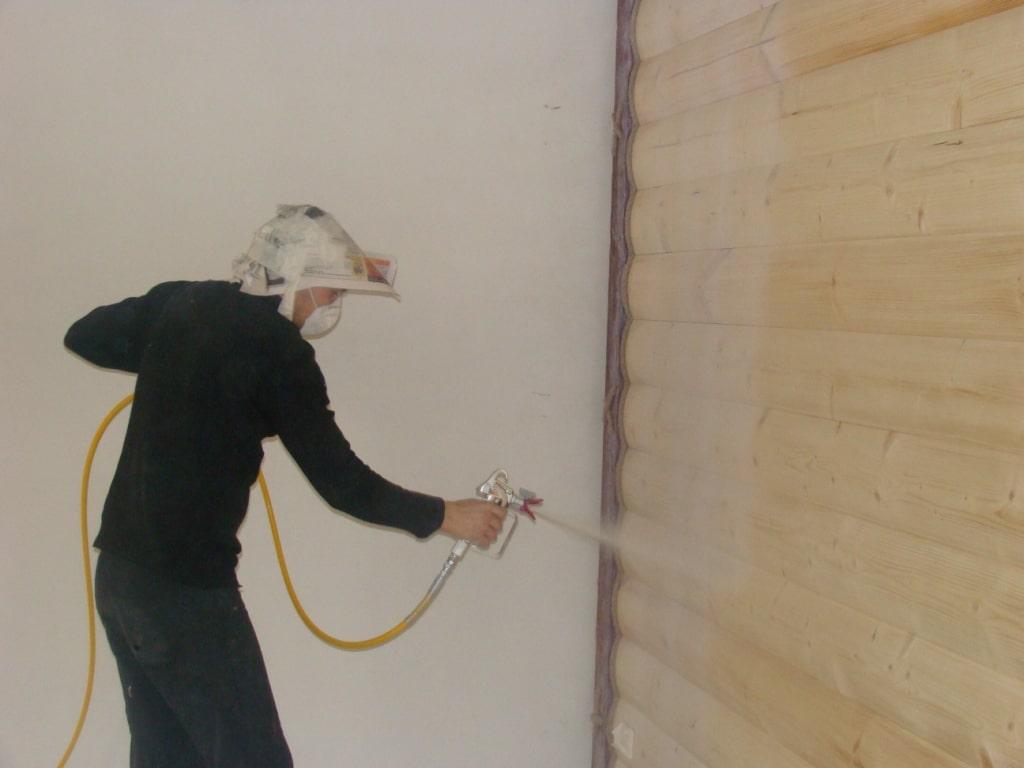На фото показан процесс нанесения лазури с помощью распылителя.