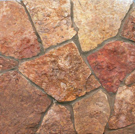 На фото - рваный камень. Он сохраняет естественную фактуру поверхности и неровные края.