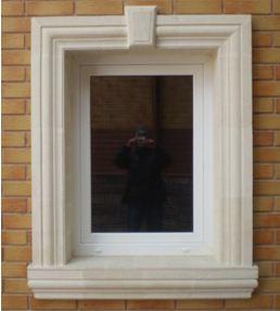 Обрамление окна на фасаде дома натуральным камнем