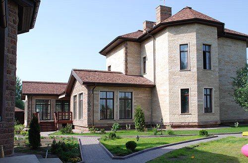 На фото - фасад дома, выполненный из искусственного камня.