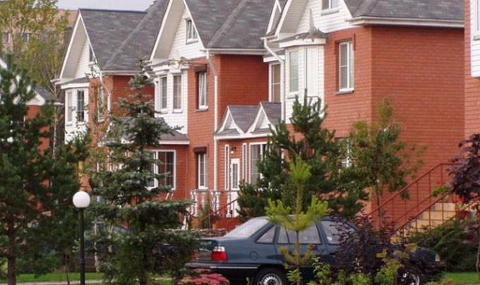 Дом с синей крышей и фасадным сайдингом белого цвета