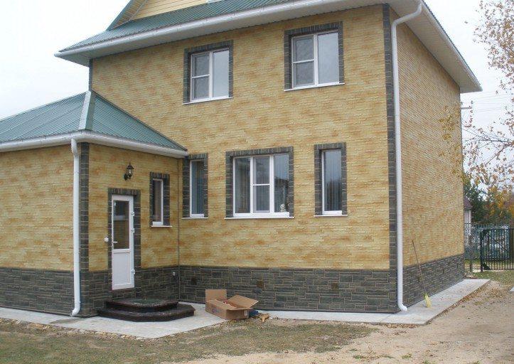 Дом с облицовкой сайдингом под камень комбинированного цвета.